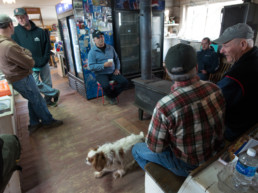 Harpswell fishermen sitting around woodstove at Watson's General Store