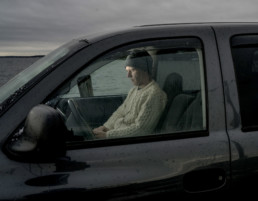 man sitting in car in rain