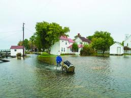 man pushing luggage through ankle-deep water