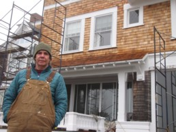 man standing in front of house with scaffolding