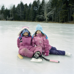two young girls sitting on ice with hockey sticks