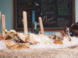 oysters on a bed of ice with a menu board in background