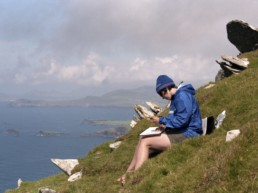 Woman sketching on a hill overlooking ocean