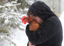 young girl hugging chicken