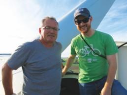 two men sitting on a wind turbine