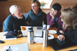 four people sat around a table conversing over a laptop