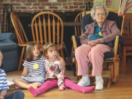 elderly woman sitting with two young girls