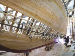 man working on building bottom of wooden boat