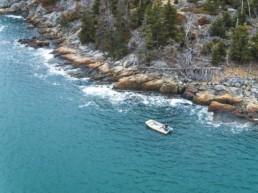 aerial shot of dinghy floating along rocky coastline