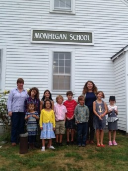 teachers and small group of students posing in front of schoolhouse building