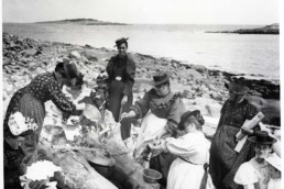 old photo of people having a picnic on a rocky beach