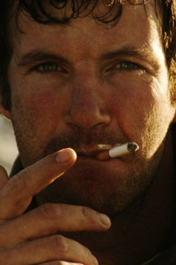 close up portrait of a man smoking a cigarette