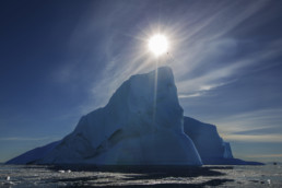 pointy iceburg with sun above