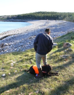 man with dog standing in front of rocky beach