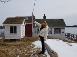 woman pointing at small white building