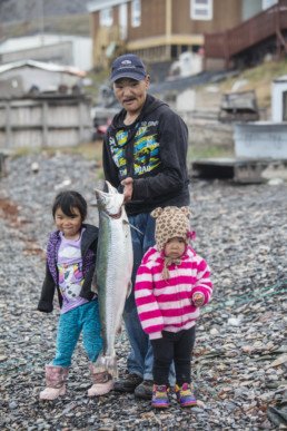 man holding salmon with two young daughters
