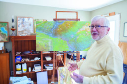 man explaining a painting on an easel