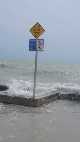 a flooded walkway with sign that reads