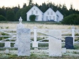 old marble headstones, white house in distance