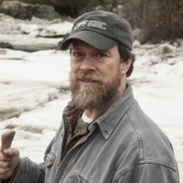 bearded man wearing hat that reads