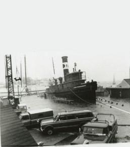 old photo of tug boat crashed into a parking lot