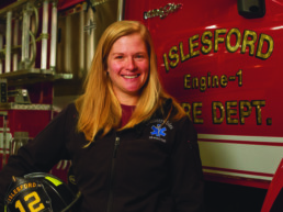 female firefighter posed in front of fire truck