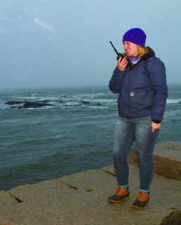 woman standing in front of ocean speaking into walky talky