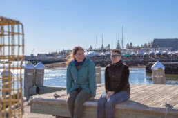 two smiling women sitting on a dock