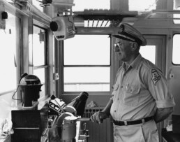 black and white photo of man captaining ferry