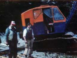 old color photo of two men in shoeshoes standing in front of excavator