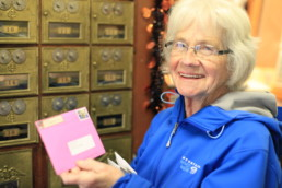 smiling old woman holding pink envelope