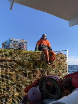 man sitting on pile of lobster traps