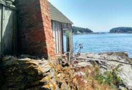 side of a shack on rocks on the ocean