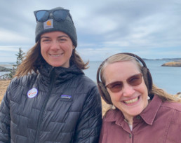 two smiling women in winter clothing in front of ocean