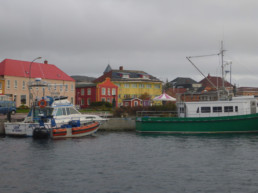 boats docked in front of colorful buildings on cloudy day