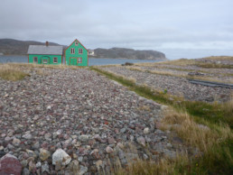 bright green house on coast with yard full of rocks