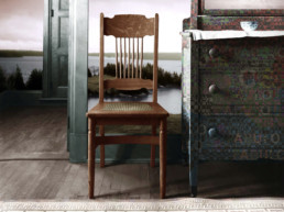 altered photo of chair in room with coastal landscape on wall