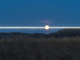 landscape art installation, line of light along horizon, striking through full moon